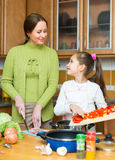 Girl and mom with vegetables Stock Photography