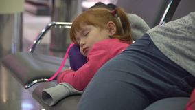Girl and momsleeping at the airport waiting area. flight delay.  stock video footage