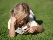 Girl with Money. Girl laying on the grass with 500 CZK stock photo