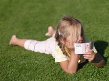 Girl with Money. Barefoot girl laying on the grass with 500 CZK stock image