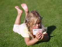 Girl with Money. Barefoot girl laying on the grass with 500 CZK royalty free stock photo