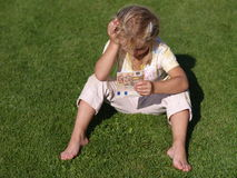 Girl with Money. Barefoot girl sitting on the grass with 100 EUR stock images