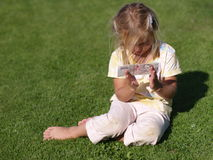 Girl with Money. Barefoot girl sitting on the grass with 500 CZK royalty free stock image