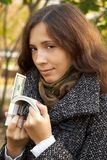 Girl with money. Young girl holding roll of dollars in her hands Royalty Free Stock Photo