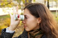 Girl with money. Young girl watching through bank-note rolled in a telescope Royalty Free Stock Photos