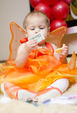 Girl with money. Girl dressed as butterfly with two dollars in a hand royalty free stock photography