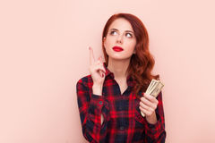 Girl with money. Surprised redhead girl in red tartan dress with money on pink background Stock Photo