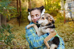 Girl and mongrel dogs. Autumn. A girl is holding a mongrel dog in her arms. Mistress and home pet for a walk in the autumn park. Caring for animals Stock Photography