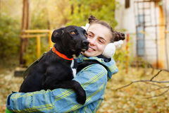 Girl and mongrel dogs. The girl holds a black mongrel dogs. Autumn day. Caring for animals Stock Photo