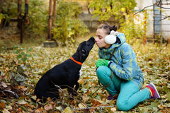 Girl and mongrel dogs. A girl kisses a black mongrel dog. Autumn day. Caring for animals Stock Photo