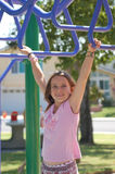 Girl On Monkey Bars. A 9 year old girl playing on the monkey bars in a park Royalty Free Stock Image