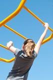 Girl on monkey bars. Girl crossing elevated monkey bars Stock Photo