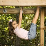 Girl on monkey bars. Side view of Hispanic girl hanging by arms and legs from monkey bars smiling at viewer Royalty Free Stock Photo