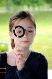 Girl with monocle. Girl with toy monocle  posing in front of a photo-booth Royalty Free Stock Images