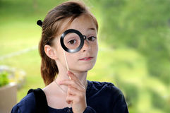 Girl with monocle. Girl with toy monocle  posing in front of a photo-booth Stock Photo