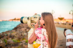 Girl and monocular, looking on the sea Royalty Free Stock Images