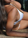 Girl in monokini laying on a longe chair Stock Image
