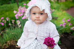 Girl 8 months old European Ukrainian little baby on a walk in the garden holds a flower and strawberries in her hands Stock Photography