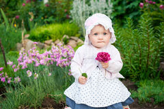 Girl 8 months old European Ukrainian little baby on a walk in the garden holds a flower and strawberries in her hands Stock Photos