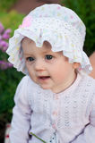 Girl 8 months old European Ukrainian little baby on a walk in the garden holds a flower and strawberries in her hands Royalty Free Stock Photo