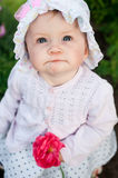 Girl 8 months old European Ukrainian little baby on a walk in the garden holds a flower and strawberries in her hands Stock Photo