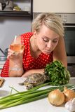 Girl mops surprised on tortoise who is eating salad. Female is surprised on tortoise who is eating salad Royalty Free Stock Photo