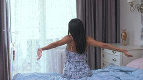 Girl in the morning on the bed. A girl sitting in bed is pulled up early in the morning stock video footage
