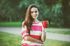 Girl with morning coffee in park Royalty Free Stock Photography