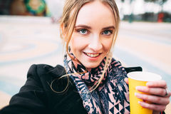 Girl with morning coffee taking selfie outside. Young attractive woman in a black coat with a cup of coffee taking selfie in a park Royalty Free Stock Images