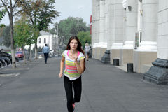 Girl on a morning jog listening to music. She is dressed in sportswear and she runs down the sidewalk in the city Royalty Free Stock Images