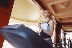 Girl on the morning run on the treadmill in the gym in front of a large window on the background of the sea.  stock image