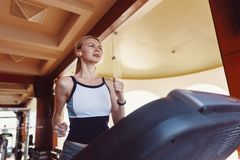 Girl on the morning run on the treadmill in the gym in front of a large window on the background of the sea.  royalty free stock image