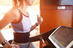 Girl on the morning run on the treadmill in the gym in front of a large window on the background of the sea.  royalty free stock photography