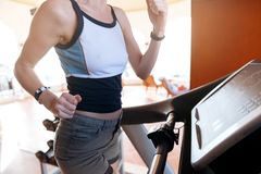 Girl on the morning run on the treadmill in the gym in front of a large window on the background of the sea.  royalty free stock photo