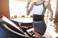 Girl on the morning run on the treadmill in the gym in front of a large window on the background of the sea.  royalty free stock images