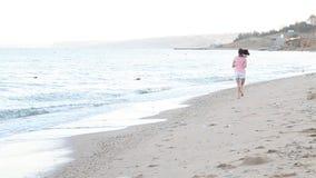 Girl in the morning runs along the beach near the sea stock footage