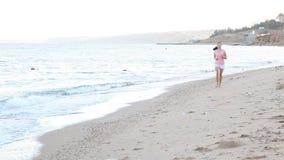 Girl in the morning runs along the beach near the sea stock video footage