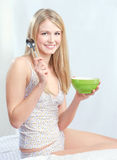Girl and mornning meal. Pretty blond girl sitting on bed and holding spoon and morning meal stock images