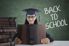 Girl with mortarboard and books back to school Stock Images