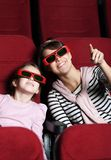 A girl with mother in 3D movie theater royalty free stock image