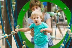 Girl with mother at action-oriented playground Royalty Free Stock Image