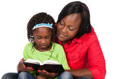 Girl and mother. Adorable small african child with braids wearing a bright green shirt and blue jeans and her mother wearing a red shirt. The mom is reading to Stock Images
