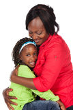 Girl and mother. Adorable small african child with braids wearing a bright green shirt and blue jeans and her mother wearing a red shirt. The mom is holding and Royalty Free Stock Photo