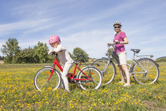 Girl with mother on bikes stock image