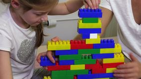 Girl and mother build tower of play bricks. In room stock footage