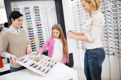 Girl with mother choose eye frames Royalty Free Stock Photography