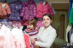 Girl with  mother chooses wear at  store Royalty Free Stock Photo