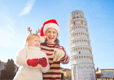 Girl with mother in Christmas hat pointing in camera. Pisa Stock Photography