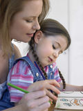 Girl And Mother Coloring Book At Home Royalty Free Stock Photography