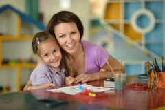 Girl with  mother Stock Images